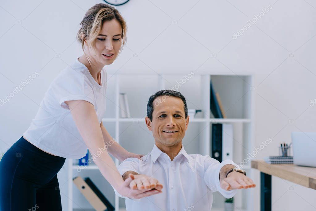 handsome adult businessman doing exercise with trainer at office