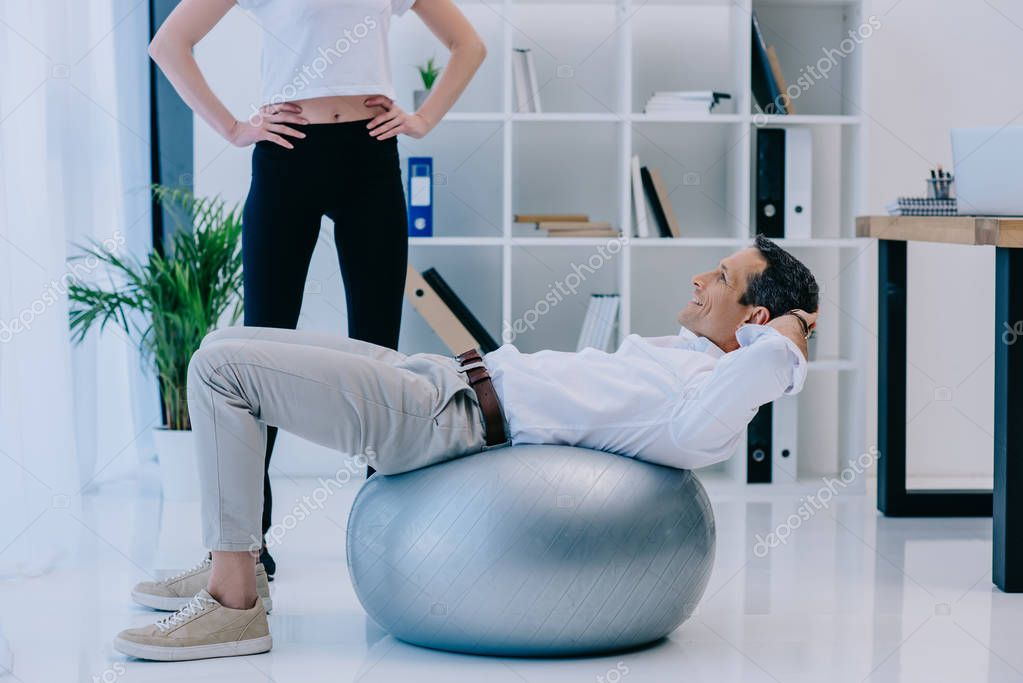 businessman working out on fit ball with female personal trainer