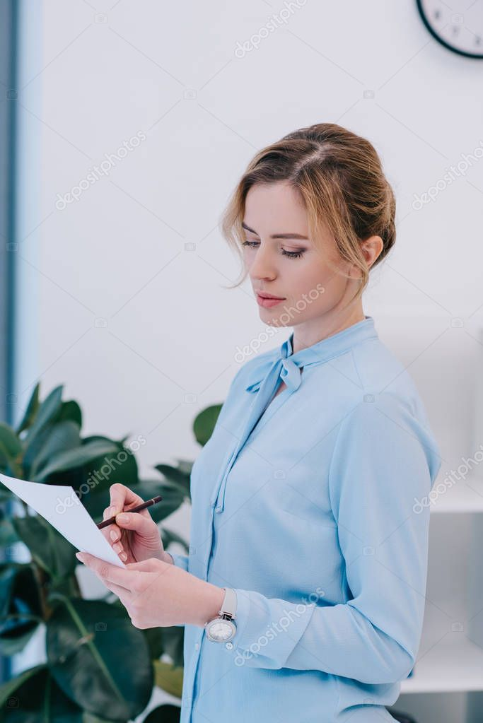 attractive businesswoman with pencil reading document