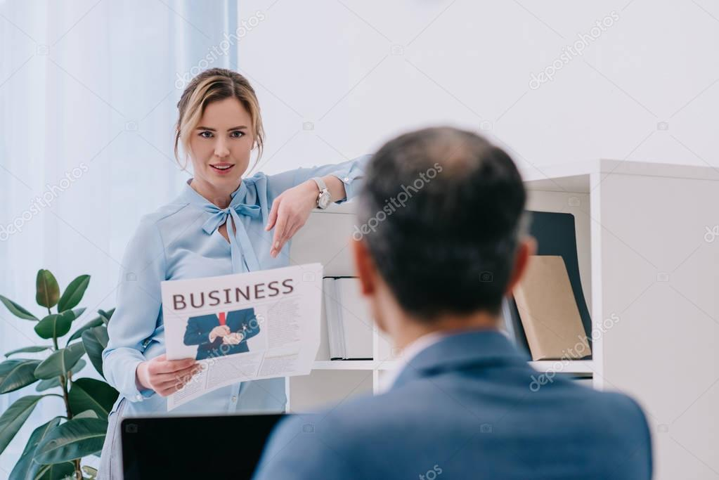 attractive businesswoman chatting with colleague while reading newspaper at office