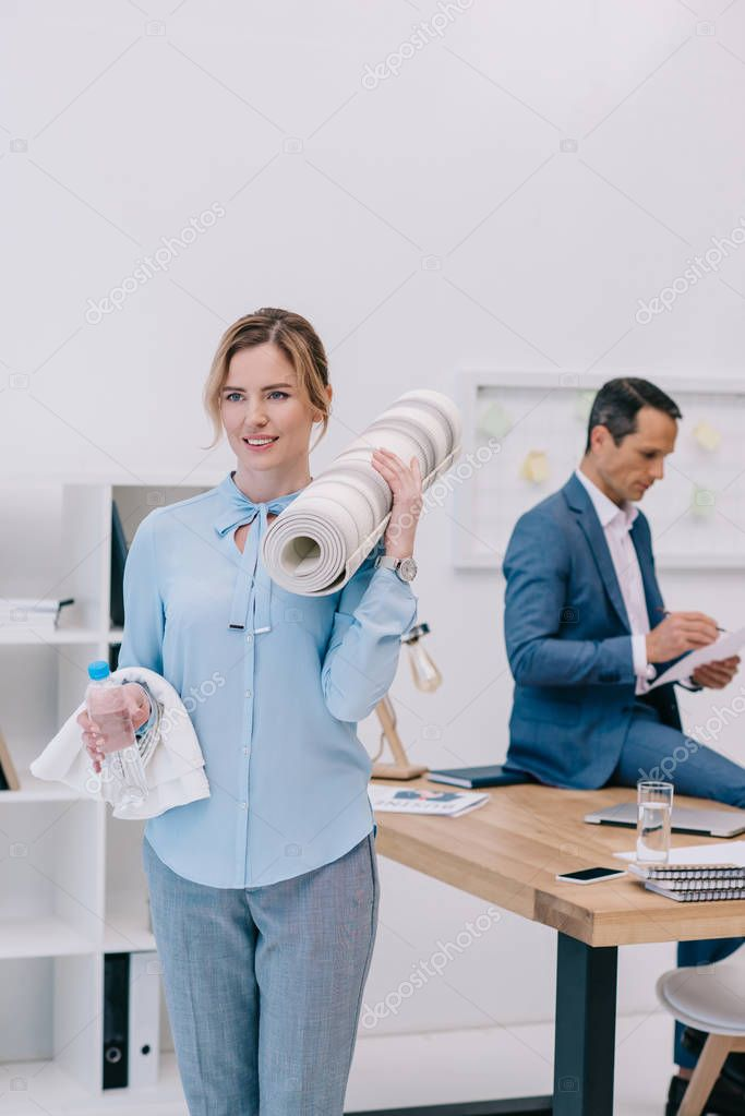 businesswoman with fitness equipment standing at modern office while her colleague working blurred on background