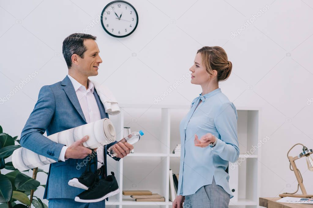 mature businessman with fitness equipment chatting with colleague before training at office