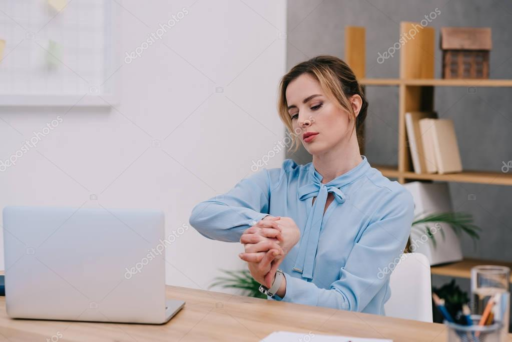 attractive businesswoman stretching hands at workplace in office
