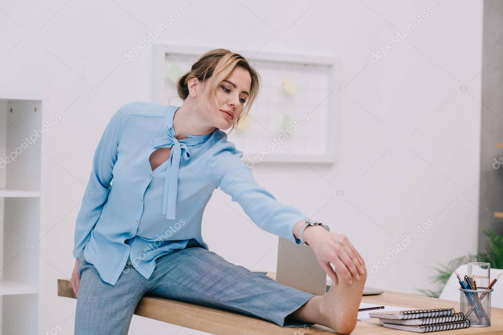 attractive businesswoman stretching on work table at office