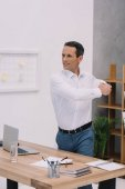 Photo healthy mature businessman stretching at his workplace in office
