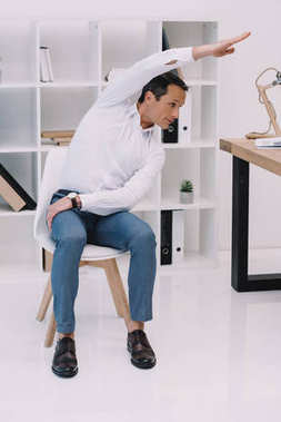 mature businessman doing side bend on chair at office