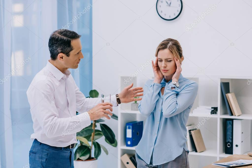 attractive businesswoman has headache while her colleague trying to help her at office