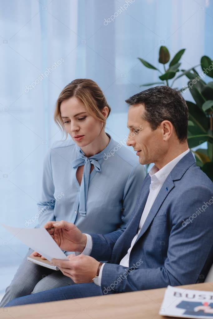 mature businesspeople doing paperwork together at office