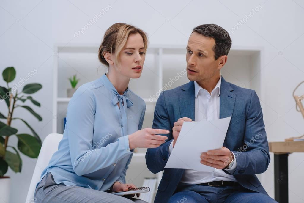 confident businesspeople doing paperwork together at office
