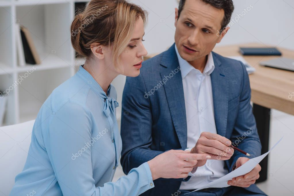 mature businesspeople discussing documents at office