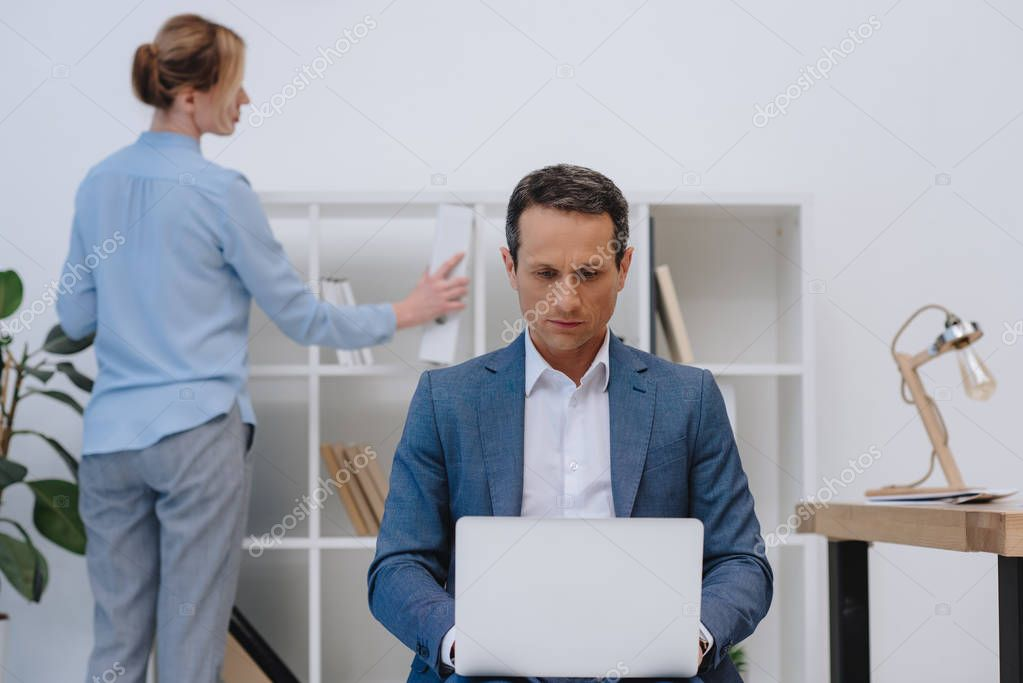 businessman working with laptop while his colleague searching for documents on bookshelves at modern office