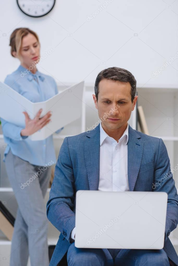 businessman working with laptop while his colleague reading documents at modern office