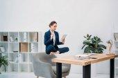 donna di affari using digital tablet mentre levitante sul posto di lavoro