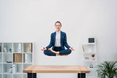 smiling young businesswoman with closed eyes meditating while levitating at workplace