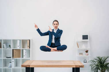 young busnesswoman pointing with fingers and looking at camera while levitating at workplace