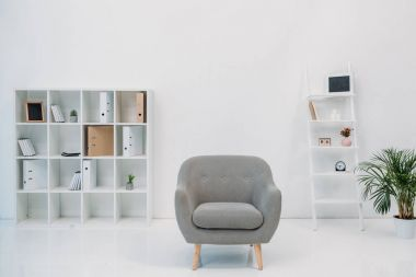 modern office interior with grey armchair and folders on shelves