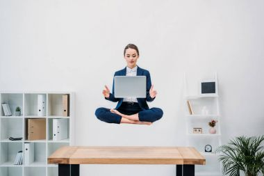 businesswoman using laptop while levitating in office