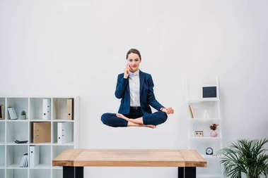 businesswoman talking by smartphone and looking at camera while levitating in office