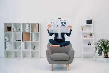 businesswoman reading newspaper while levitating in office