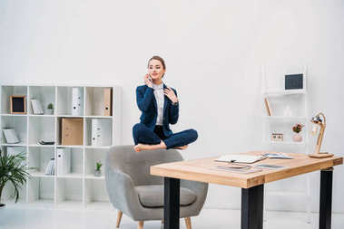 beautiful young businesswoman talking by smartphone while levitating at workplace