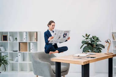 smiling young businesswoman reading newspaper while levitating at workplace