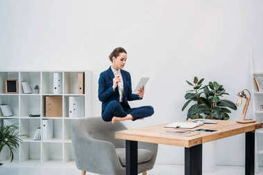 businesswoman using digital tablet while levitating at workplace