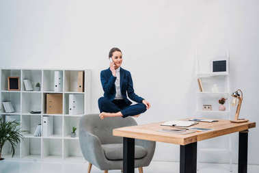 businesswoman talking by smartphone while levitating at workplace