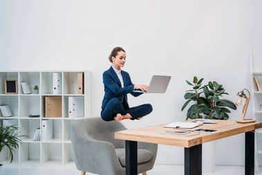 businesswoman using laptop while levitating at workplace