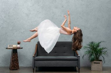 beautiful young barefoot woman hovering above sofa