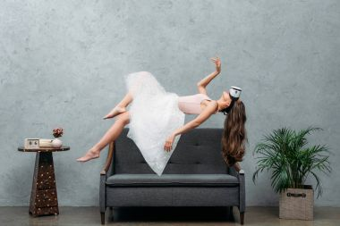 young barefoot woman in virtual reality headset levitating above couch