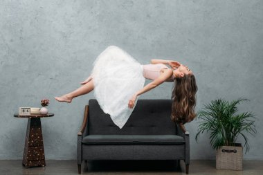 beautiful young barefoot woman levitating above couch