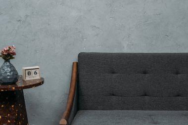 cozy empty sofa and calendar on table near grey wall