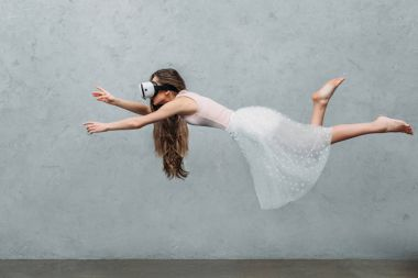 young barefoot woman in virtual reality headset levitating on grey