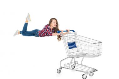 Smiling young woman levitating with empty shopping trolley isolated on white stock vector