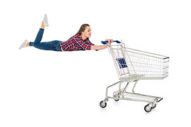 happy young woman levitating with empty shopping trolley isolated on white