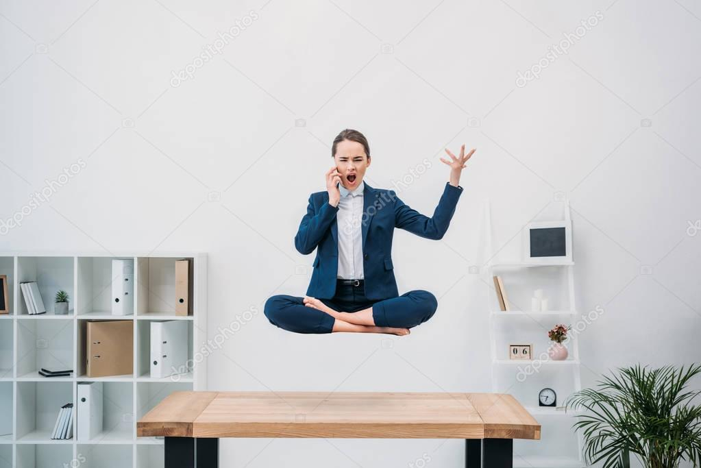 emotional young businesswoman talking by smartphone while levitating in office
