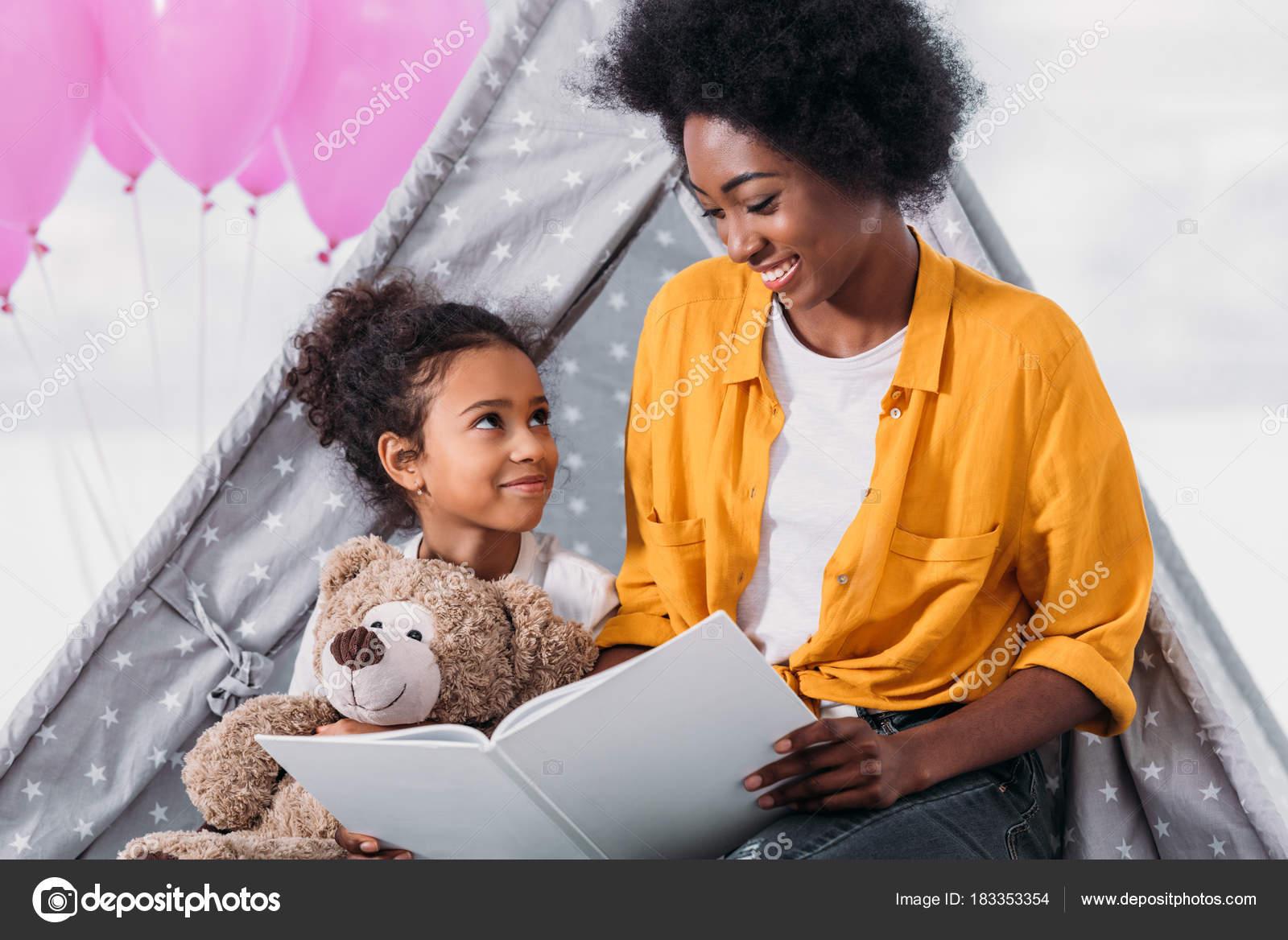 Feliz madre afroamericana e hija leer libro juntos en el hogar - descargar  libro la crianza feliz — Foto de ...