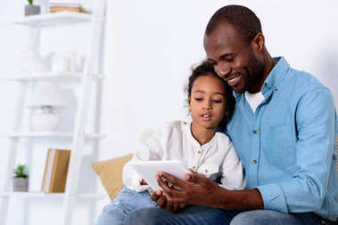 african american father and daughter watching something on tablet at home