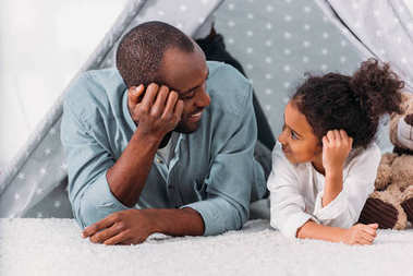 african american father and daughter lying on floor and looking at each other at home