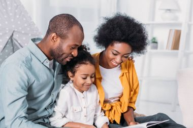 african american parents reading with daughter at home
