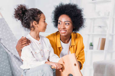 african american mother and daughter hugging daughter on rocking horse at home