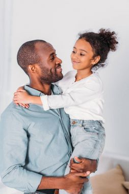 african american father carrying and hugging daughter at home