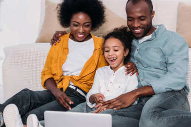 laughing african american parents and daughter watching movie on laptop