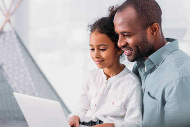 side view of happy african american father and daughter using laptop at home