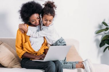 african american mother and daughter watching something on laptop at home