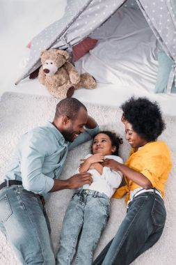 high angle view of african american parents and daughter having fun on floor at home