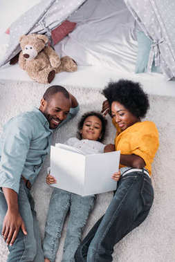 high angle view of african american parents and daughter lying on floor and reading book