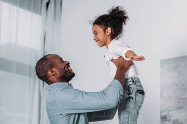 happy african american father raising daughter at home