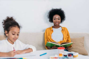 african american mother reading book and daughter drawing with felt pens at home