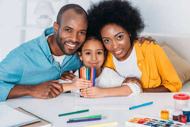 african american parents and daughter with felt pens looking at camera at home